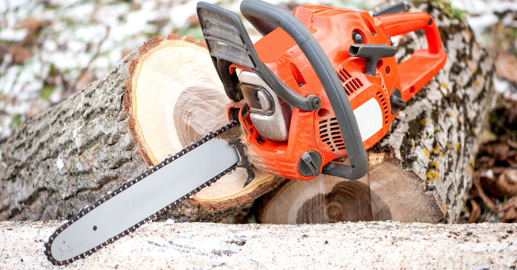 gasoline powered professional chainsaw on pile of cut wood against winter and snow background