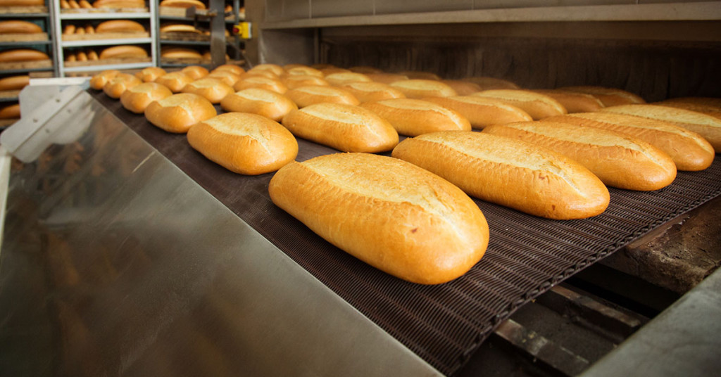 Fresh hot baked bread loafs on the production line